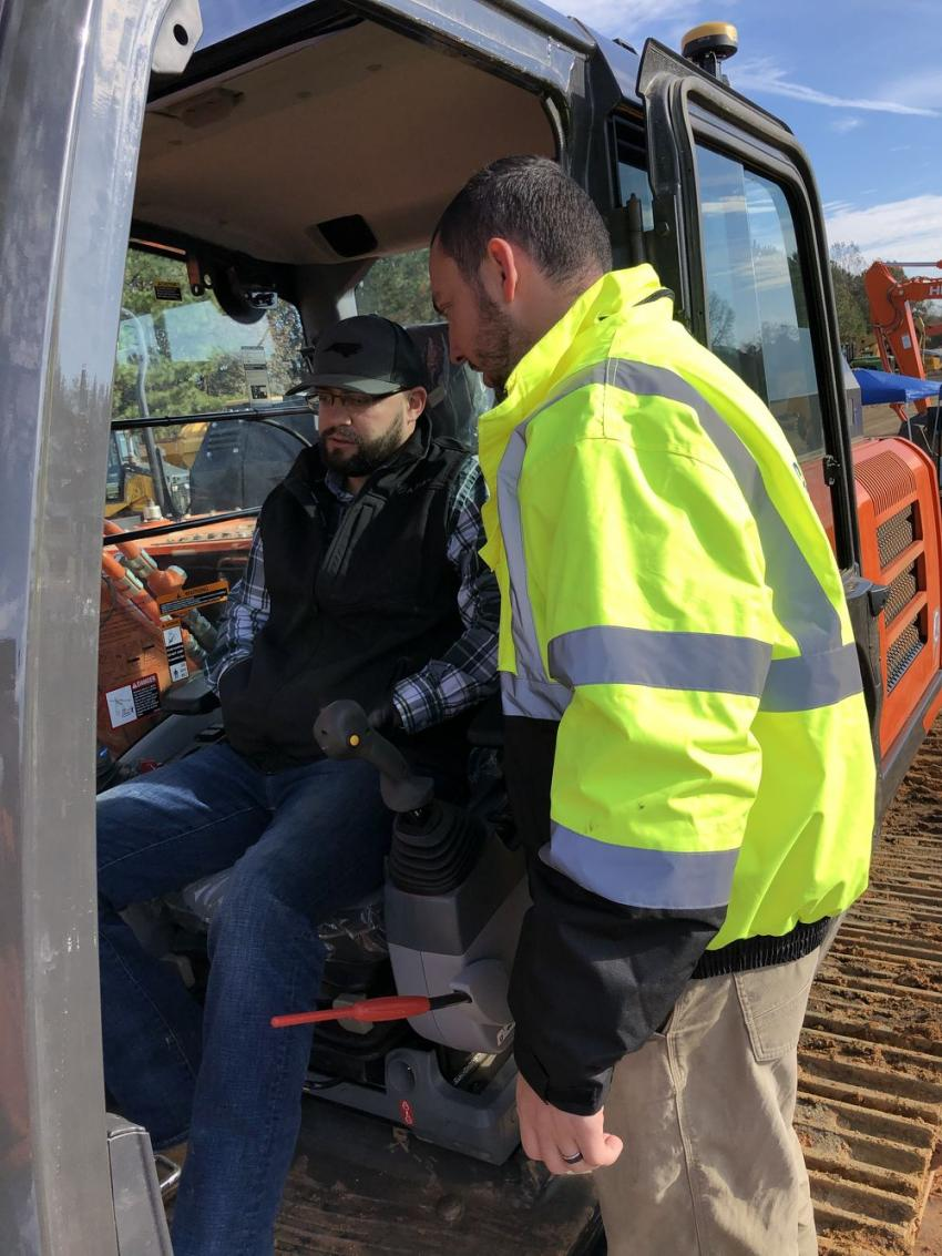 Seth Farthing (in cab) of Centerline Contracting in Monroe, N.C., learns about the productivity enhancements when using the Topcon X-53x from Thomas Etheridge of Benchmark Tool & Supply.