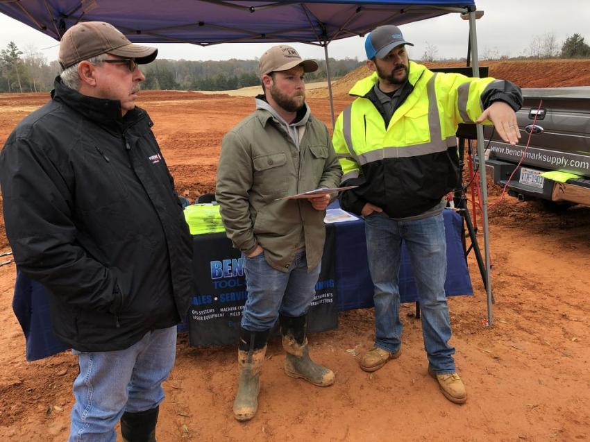 Mark and Bailey Doggett of Doggett Construction Co. in Summerfield, N.C., listen as Mike Blazek of Benchmark goes over how the Hitachi excavator functions with the Topcon X-53x