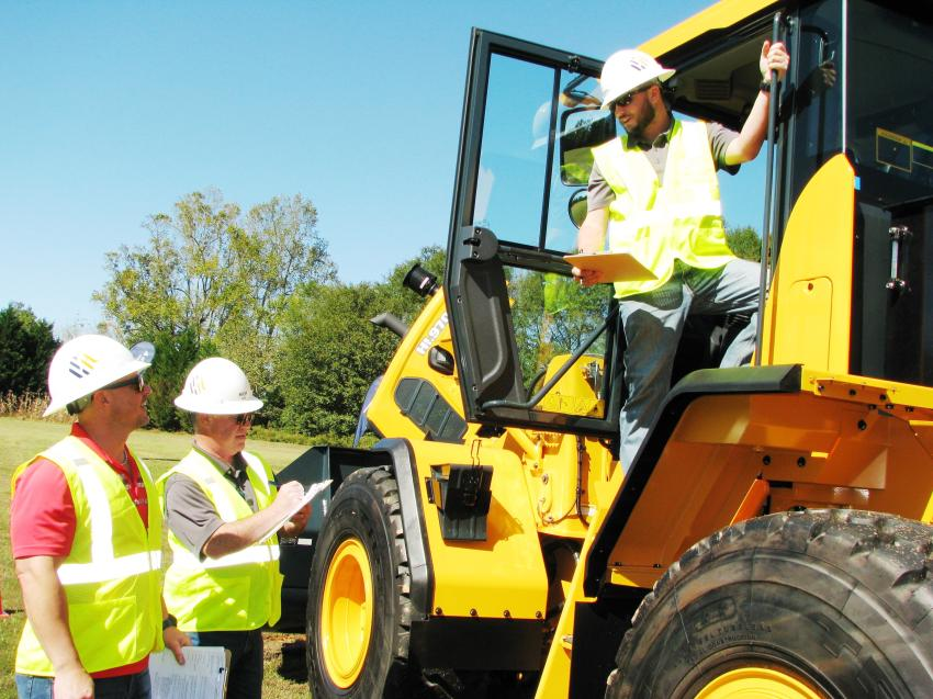 Going over the selling features of a Hyundai HL940 wheel loader (L-R) are Eric Breese, RECO Equipment, Indianapolis, Ind.; Rich Mix, Correlli Inc., Baltimore, Md.; and Matt Teets, May-RHI, Columbia, S.C.