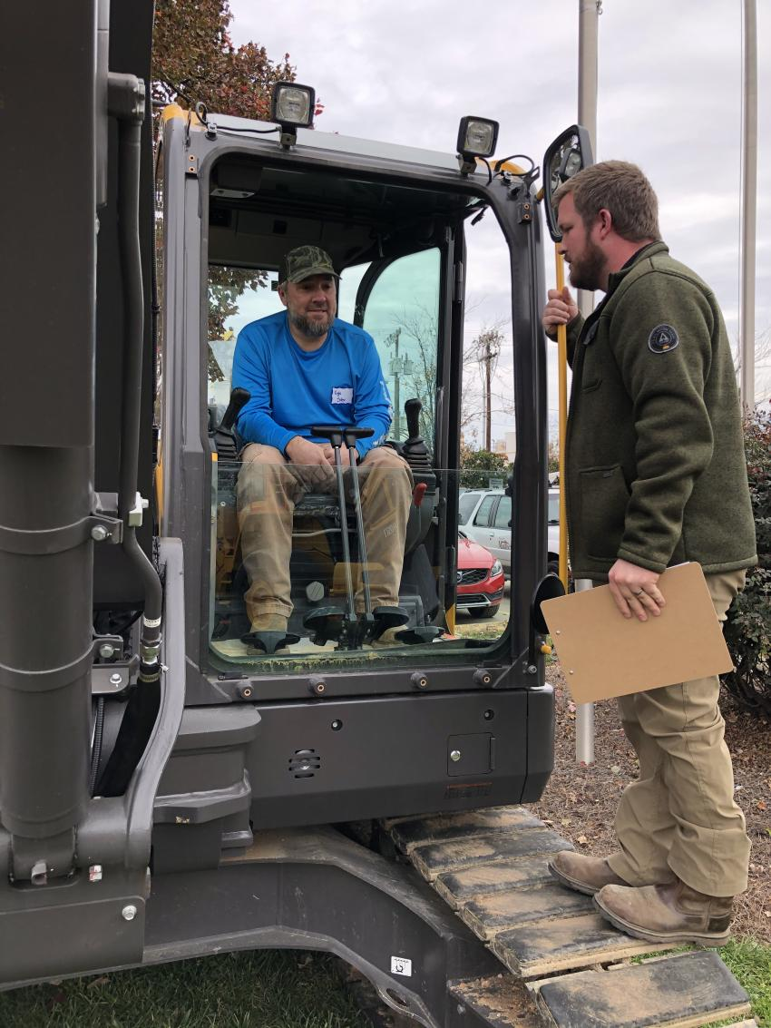 Kyle Siler (seated) of Gradexx in Trinity, N.C., gets an overview of the Volvo ECR88D from Jarred Gardner of Ascendum Machinery.