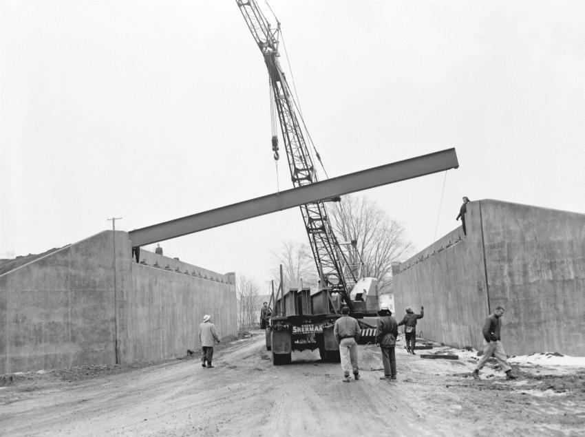 A P&H 555A-TC 35-ton truck crane lifts a steel beam into place for a single span bridge along the Connecticut Turnpike at Mill Plain Road in the Town of Branford, Conn. The prime contractor for the entire $8,384,791 turnpike project 319-01 was M. A. Gammino of Providence, R.I. The steel erection subcontractor is Harris Structural Steel of New York City. The photo taken Feb. 7, 1957, depicts a dreary wet winter day.