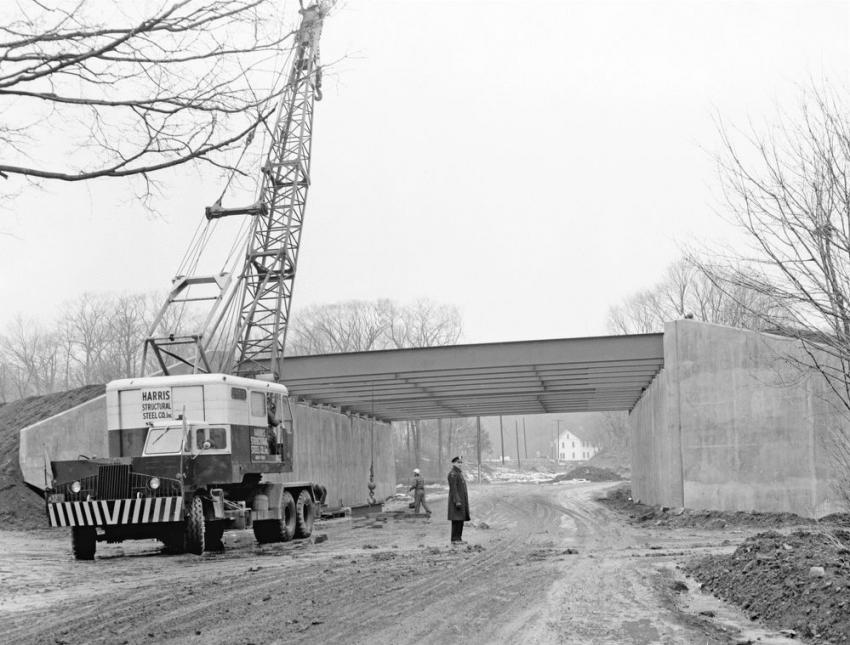All in a day's work; the steel beams are in place. A police officer on traffic detail is vigilant while the remaining braces are lifted.