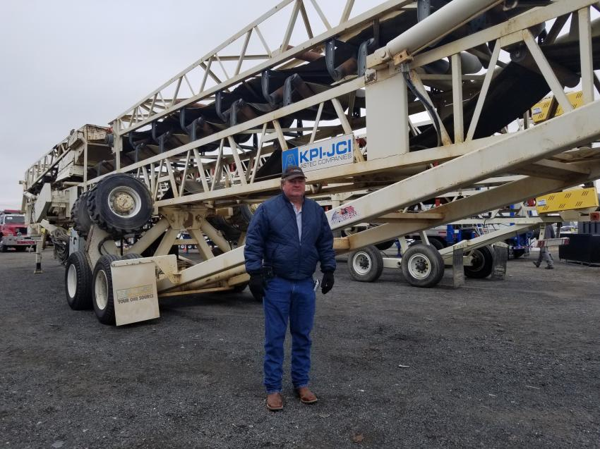 Scott Farley, of Kernen Construction, stands next to his 2010 KPI-JCI 13-36125 radial stacker he picked up at the auction.
