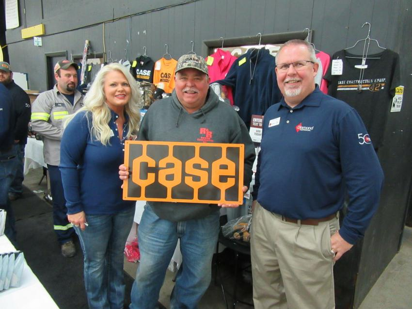 Diamond Equipment's husband and wife team, Jennifer and Jeff King, present George Johnson (C) with a door prize at the event.