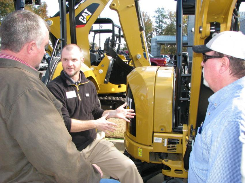 Chad Zeis and Danny Boswell of Gunter Construction, Lawrenceville, Ga., talk with their Yancey representative, Blake Jones, (center) about some compact machines of interest in the sale.