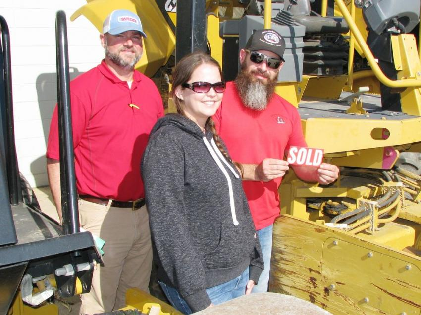 (L-R): Yancey's Phillip Martin watches as Jessica Myers and Eric Collins of Collins Site Services, Senoia, Ga., get ready to slap the SOLD sticker on a soil compactor they just purchased.