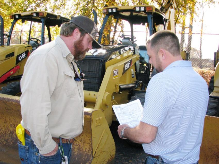 Deep in discussion of the specs of a Cat 450F backhoe loader are Jody Bennett (L) of Pro-Source Utility Contractors, Carrollton, Ga., and Andrew Gaston of Yancey Bros. Co.