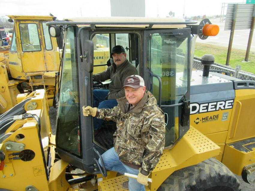 Robbie Hunt (seated) of Hunt Farms and Jeffery Morris of Morris Farms gave this John Deere 544K wheel loader a close look at the auction.