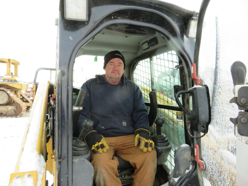 Ted Detrick of Detrick Truck and Trailer checks the cab of this Cat 279 skid steer.