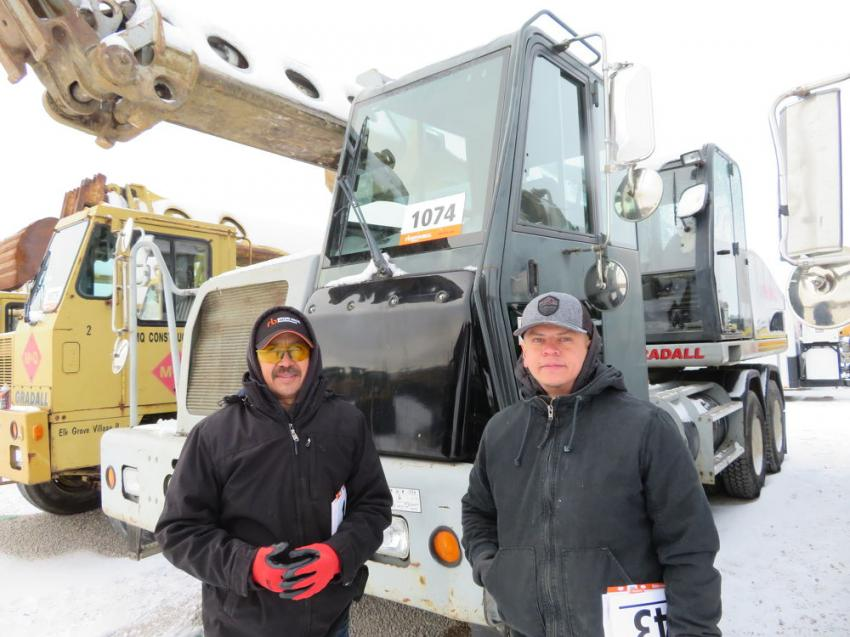 Juan Hernandez (L) and Isaiah Cruz are considering a bid on this Gradall XL 4100 wheeled excavator.