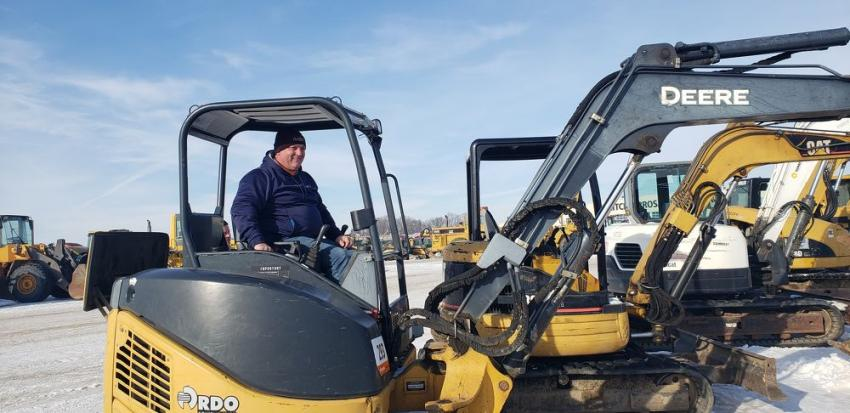 Pat Nolan, auctioneer of Old 20 Auctions, Manchester, Iowa, takes a look at this John Deere mini-excavator.