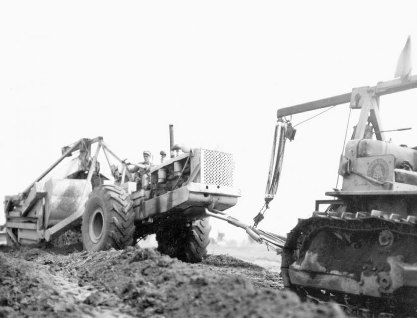 In Connecticut — A. I. Savin Construction Co. of East Hartford, Conn., snatch loading a LeTourneau Super C with a LP Carryall using shop modified Caterpillar D8 tractor while grading the Rentschler Field airport in East Hartford, Conn., during August 1944.