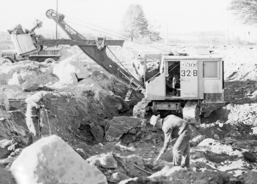 In Connecticut — C. W. Blakeslee & Sons Inc. of New Haven, Conn., using a gasoline-powered Bucyrus-Erie 32-B shovel equipped with a one yard dipper to excavate a building basement in Newtown, Conn., ca. 1930s. The single dump truck in the far left background is an International Harvester.