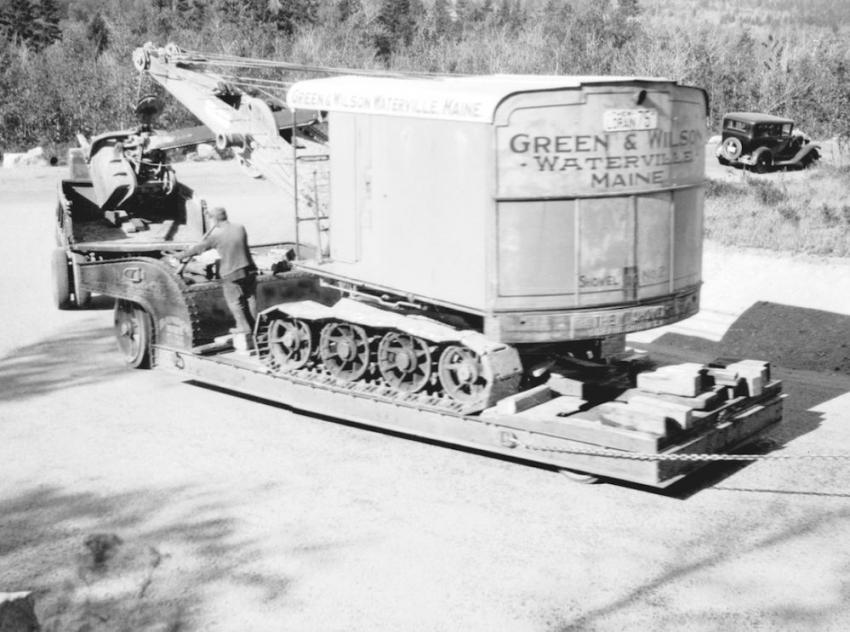 In Maine — A Thew Lorain 75 shovel is on a Rogers trailer headed down Cadillac Mountain in Acadia National Park, Maine, in the 1930s. The single axle dump trucks appear to be Internationals. The one in the rear is loaded with an air compressor for traction. It is chained to the trailer to add braking force on the steep decline. The shovel is owned by Green & Wilson of Waterville, Maine.