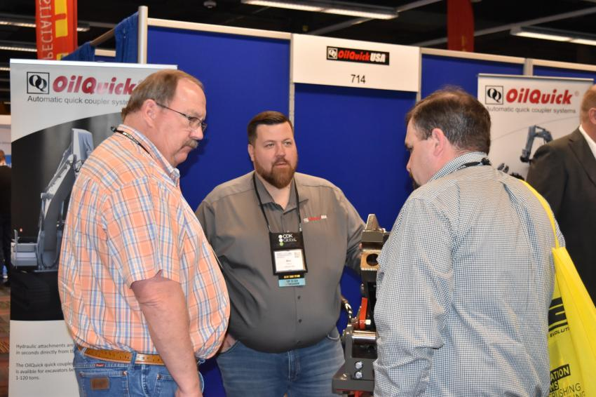 Max Verva, regional manager of the Midwest Region of OilQuick USA, talks with customers about the company's quick coupler system.