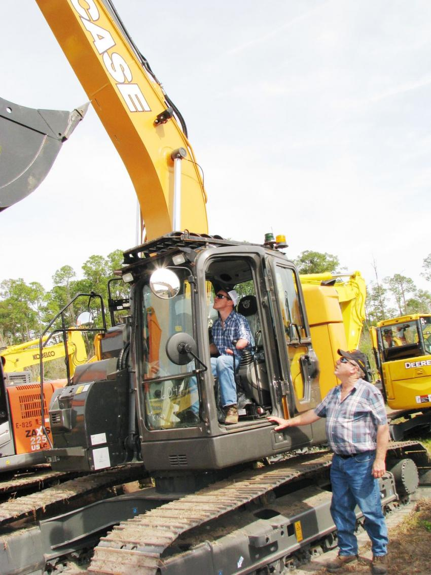 Evan Carter (L) and Andy Calder of Andy Calder Excavating of Ontario, Canada, work over a late model Case CX245D SR excavator.