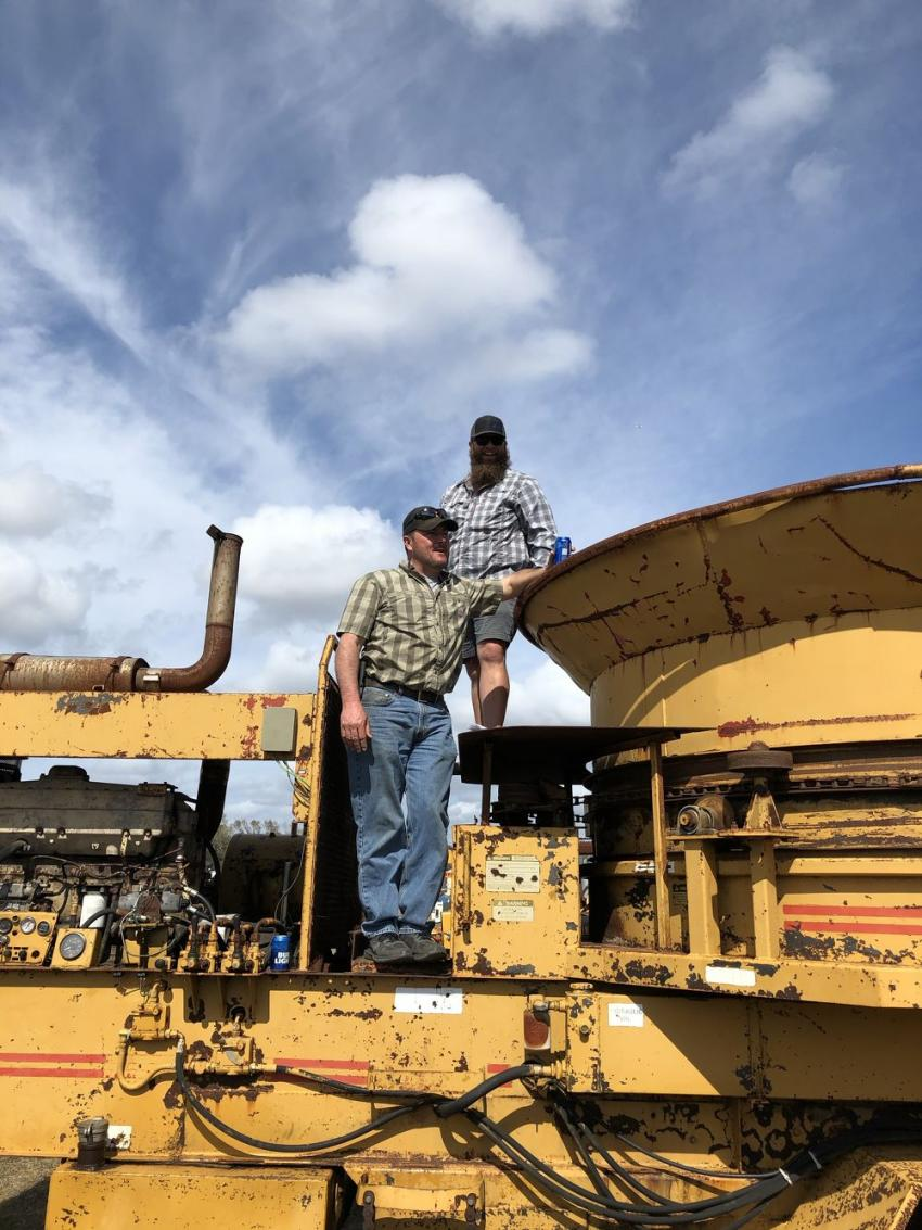 Rawlins Landscape & Grading's Scott Justice (L) and Chris Rawlins consider a bid on this Haybuster IG-11 tub grinder at the auction.