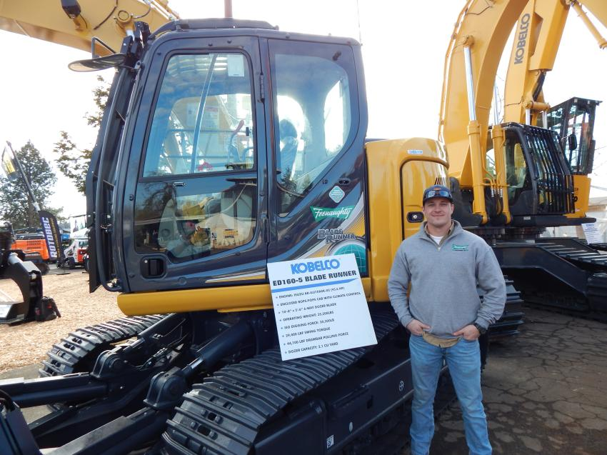 Derrick Hough, territory manager of Feenaughty Machinery Co., Portland, Ore., with the powerful Kobelco ED160-5 Blade Runner excavator which features a six-way blade for pushing material or quickly refilling a work site.