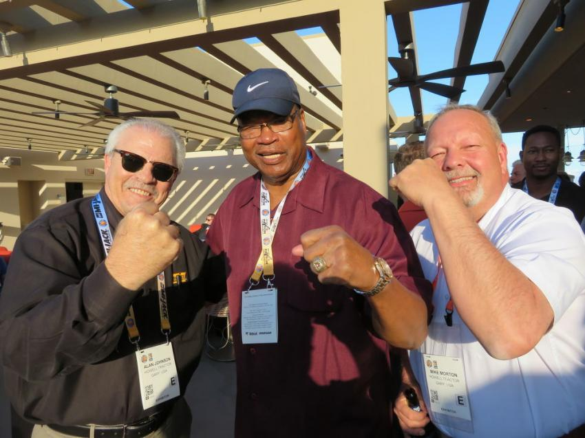 Heavyweight Boxing Champ Larry Holmes (C) takes one or two on the chin from Alan Johnson, (L), area manager of Howell Tractor, and Mike Morton, president of Howell Tractor.