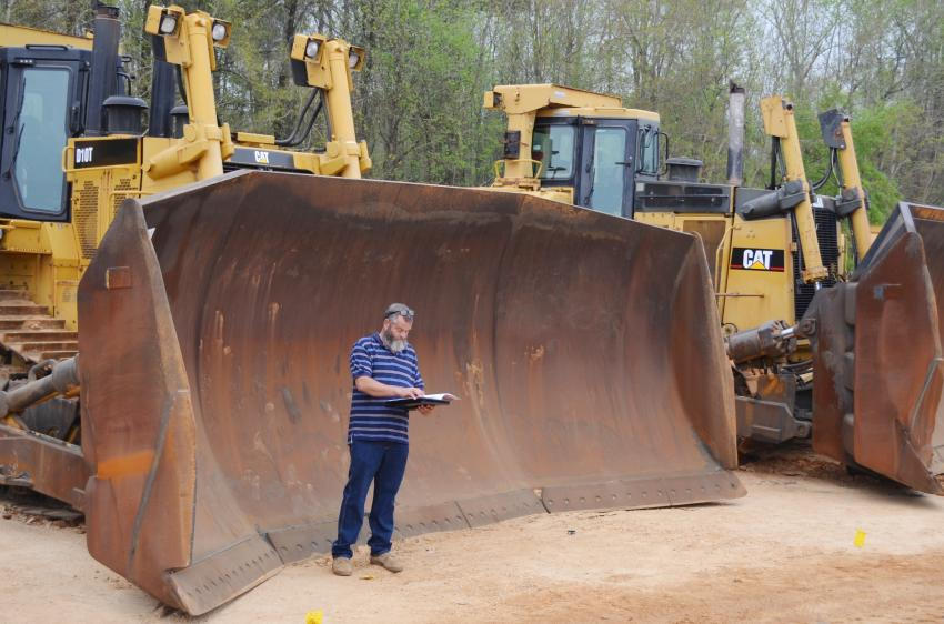 Independent contractor Shane Booth of Flomaton, Ala., is looking a little small in front of the blade of one of the Cat D10's in the sale lineup.