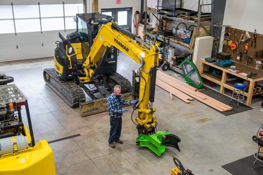 Lou Sawyer, shop foreman, oversees the installation of an OMEF hydraulic tree shear on a Yanmar excavator.