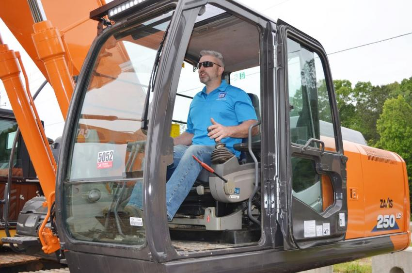 Giving a Hitachi 250LC excavator a good workout before the sale began is Damien Sherry of Greystone International, Canton, Ga.