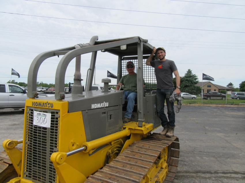 Scott Mathews (L) and Cole McMath of Northwestern Masonry Service Company consider a bid on this Komatsu D39E dozer at Yoder & Frey's North Baltimore, Ohio, sale.