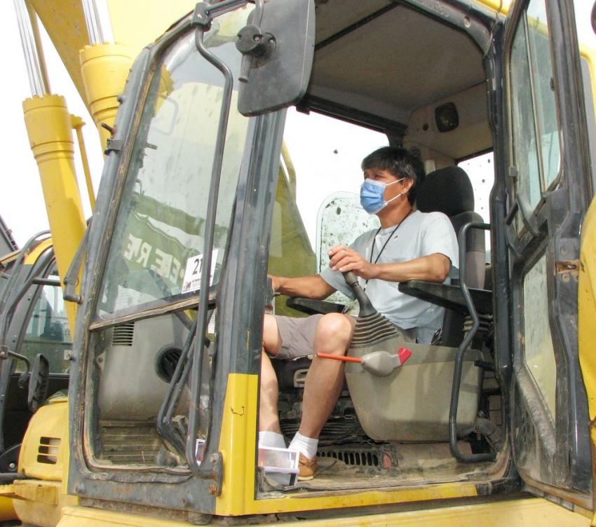Test operating several of the excavators at the auction is Khanh Nguyen of K&H Farms, Collins, Miss.