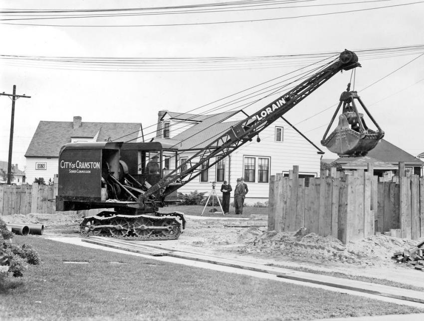 This Lorain 40A clamshell crane operates with a flattened boom angle to avoid utility lines on a sewer job in Cranston, Rhode Island, circa 1940. Note the trench sheathing.