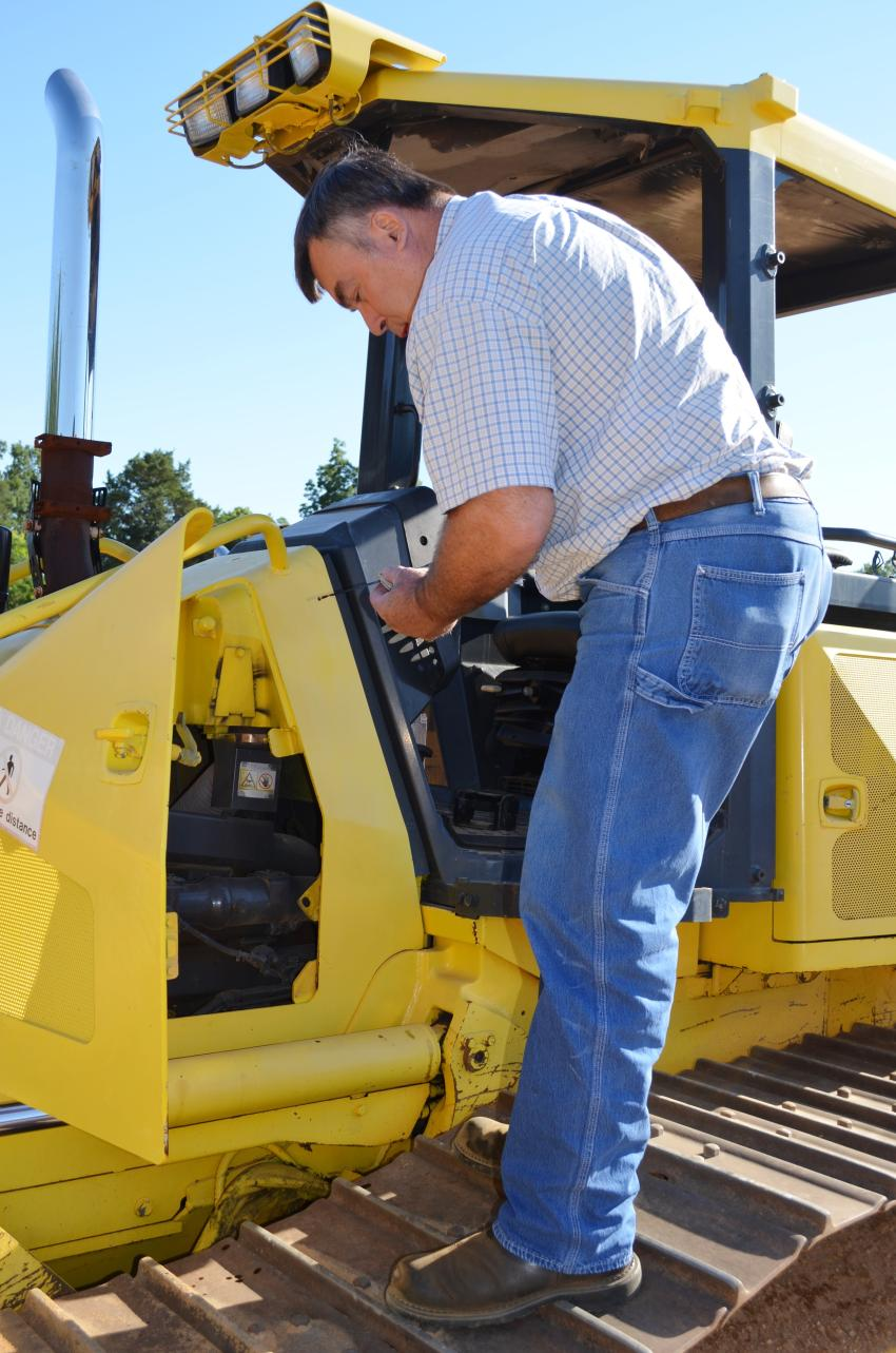 Wendell Cain of Cain & Todd Equipment, Lilburn, Ga., checks the fluids and overall condition of a Komatsu D51PX dozer of interest.