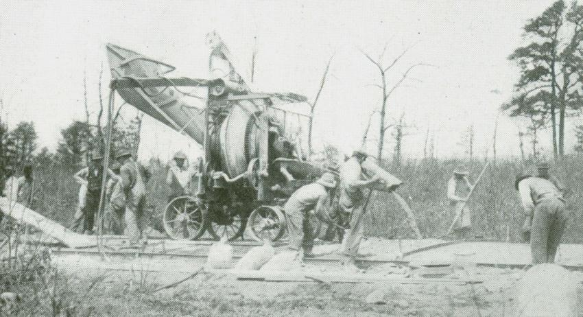 "The earliest dry batch pavers were simple mixers like this Foote 5A traction paving mixer, working on the Vanderbilt Motor Parkway on Long Island. It receives dry materials at one end of its chassis, or truck, and discharges concrete to the other. Note the fixed, non-tilting drum; it is of Foote's unique double-cone design. A laborer at left appears to be repositioning a plank for the paver to travel on, and the ""finisher"" is a simple screed.