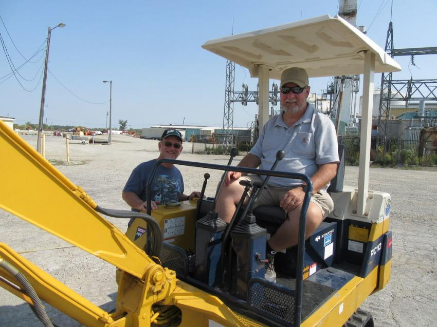 Scott Ford (L) and Steve Lievestro of Grand View Farms try out this Komatsu PC10 mini-excavator.