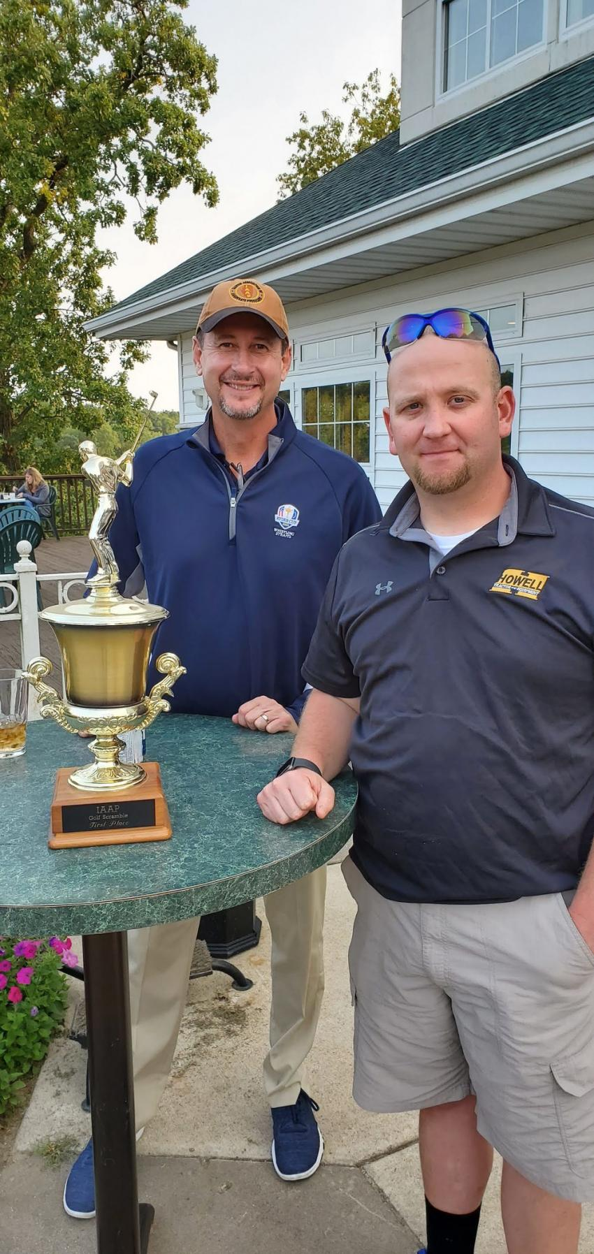 IAAP's Dan Eichholz (L) presents the first-place trophy to the Howell Tractor team's Aaron King.