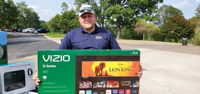 Ed Ellis of Roland Machinery took home this Vizio TV, one of many raffle prizes.