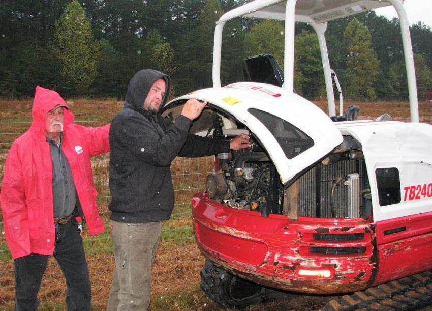 Inspecting a Takeuchi TB240 compact hydraulic excavator while dodging a few raindrops are Dale Henderson (L) of Henderson Equipment, Blairsville, Ga. and Kyle Henderson  of KC Construction, Murphy, N.C.