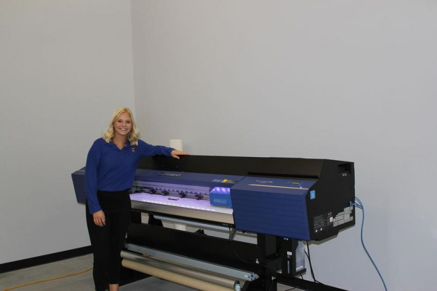 """Maddie Thilges, new marketing coordinator of Mid Country, shows off the new Roland VGZ 540 graphics printer used to create equipment and vehicle graphics for the dealership and its customers. """"This has been a great investment,"""" said Thilges. """"We can do our own vehicle and equipment graphics, banners, signs and much more."""""""