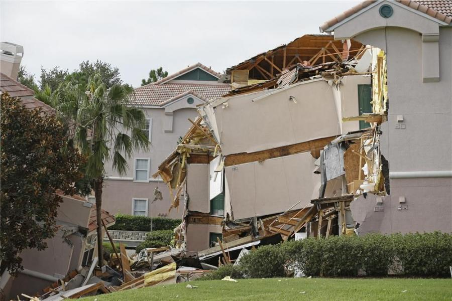 Damage to buildings caused by a sinkhole 40 to 50 in diameter is seen at the Summer Bay Resort, Monday, Aug. 12, 2013, in Clermont, Fla.(AP Photo/John Raoux)
