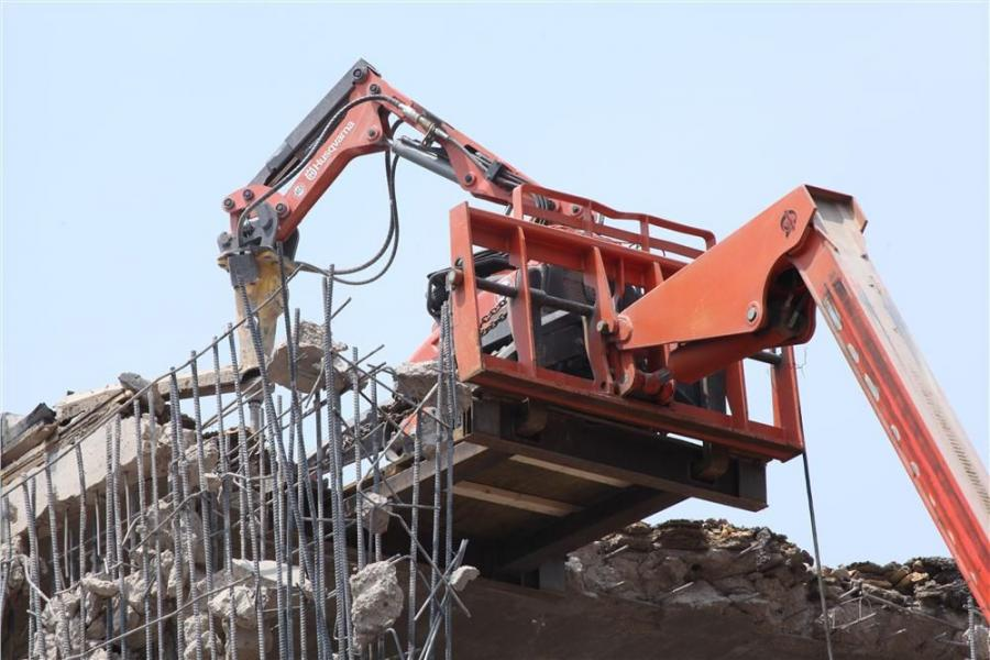 A Husqvarna backhoe hammers away at the roof of the McKnight Theater in the early stages of the demolition operations.