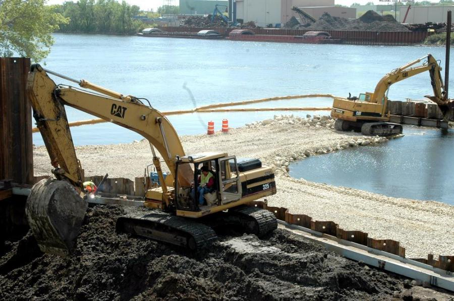 One Cat backhoe excavates a cofferdam for one of the bridge piers while the other is building an access road into the river.