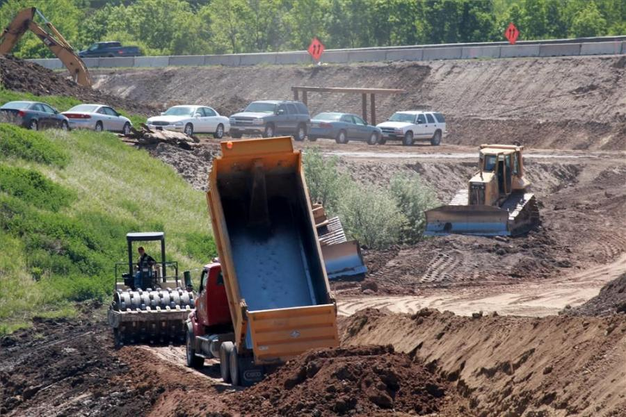 Cat dozers and a roller move fill near mainline I-694 early in the second season of construction to improve a busy interchange north of St. Paul, Minn.