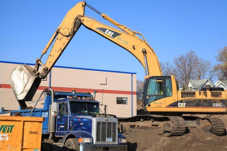 During soil removal work, the operator of a Cat 330C excavator dumps soil into a truck. Approximately 3,000 cu. yd.  (2,300 cu m) of soil was removed  while preparing the base of  the construction site for  the new addition.