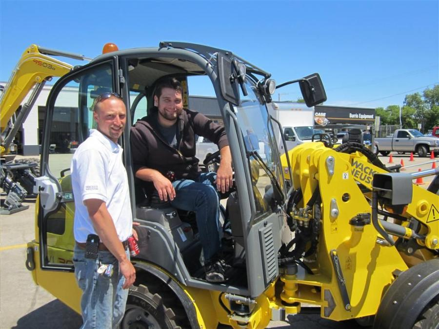 Bryan Heinrichs (L) of Burris Equipment shows the Wacker Neuson WL 30 compact wheel loader to Emory Patterson of Emory Patterson Construction.