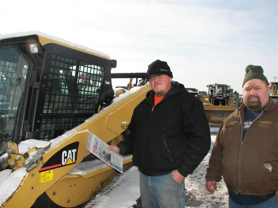 Travis Wood (L) of Wood Brothers Blacktop, Princeton, Minn., and Clarence Tulp of Kirshman Excavating, Cambridge, Minn., take a close look at this Cat track machine.