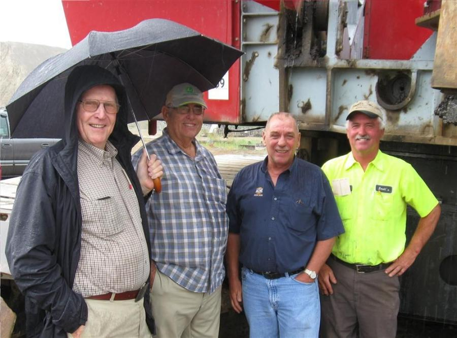 (L-R): George and Bill Small, along with Terry Stewart of Acme Machinery, join Mike Small of Small Sand & Gravel to find a spot out of the rain while keeping up with the auction.