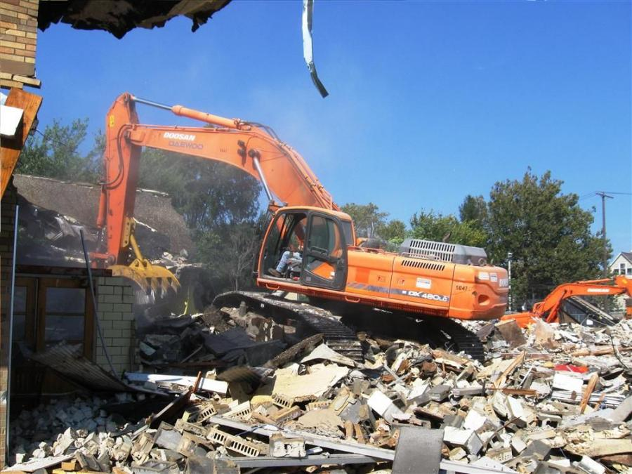 The Doosan DX 480 excavator equipped with an Aim Attachments grapple makes quick work of this section of wall.