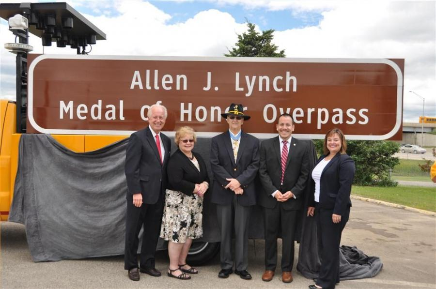 (L-R): State Sen. Terry Link, former State Rep. JoAnn Osmond, Allen J. Lynch, Illinois Department of Veterans Affairs Assistant Director Rodrigo Garcia and Illinois Tollway Executive Director Kristi Lafleur stand in front of Grand Avenue Bridge sign.