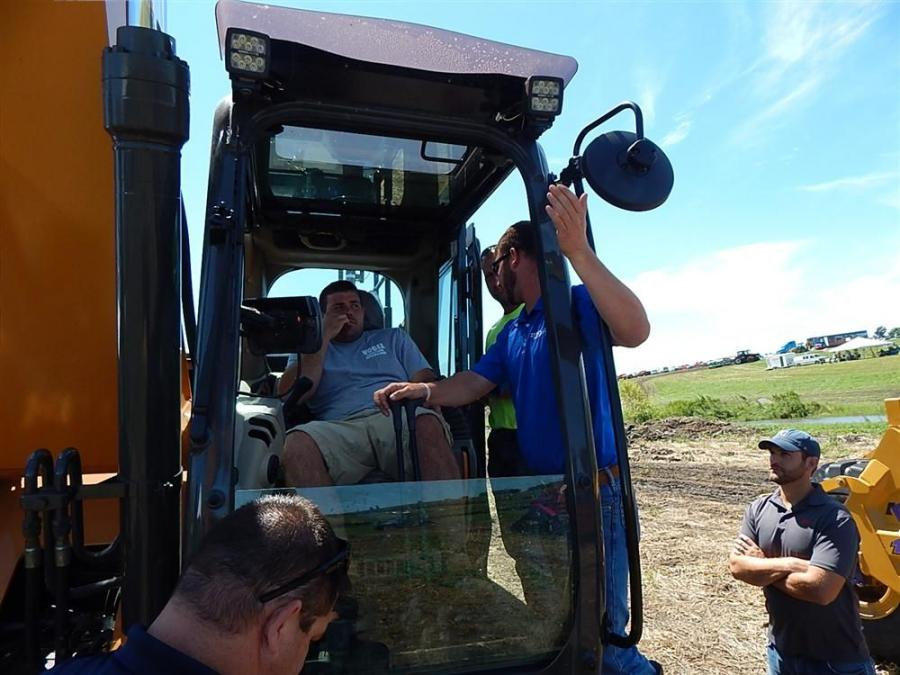 (L-R): Brice Blair of B&S Tiling, Lake City, Iowa, gets the rundown on the ICON 3D excavator control system on a Case 250D from Darrin Brown, Titan Machinery machine control specialist, while Titan Machinery Field Marketer Mike Hoffman looks on.