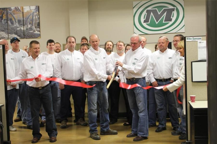 Minnich Manufacturing Plant Manager Troy Kingan and owner Jim Minnich are cheered on by company employees as they cut the ribbon.