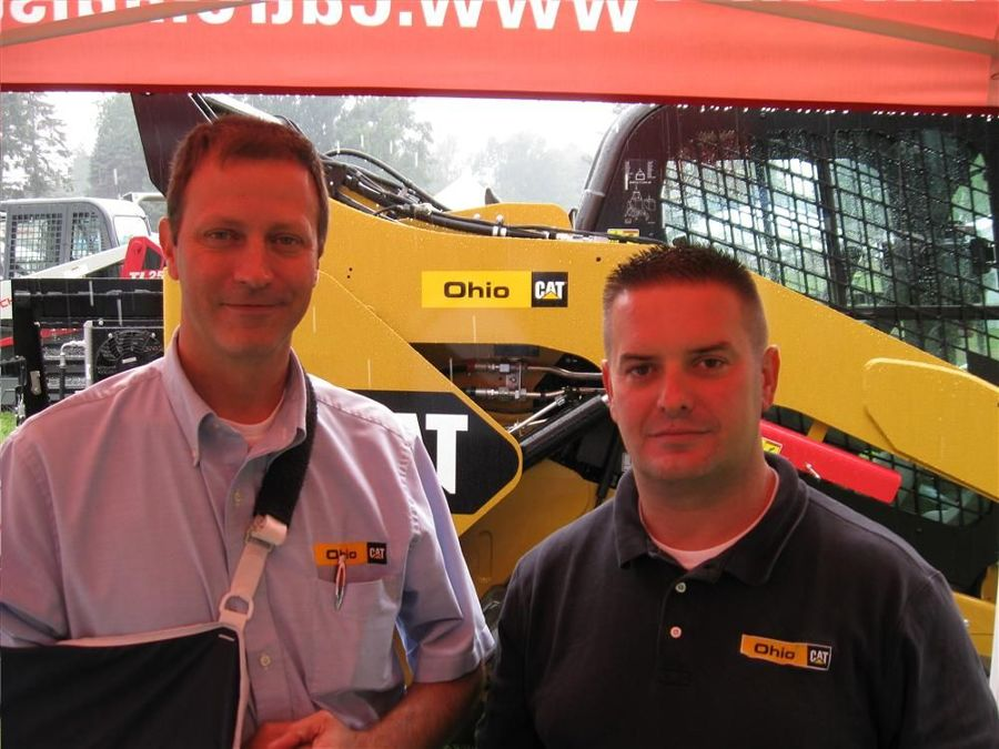 Ohio CAT's Art Westfall (L) and Brian Gillard stay dry while talking to attendees about the company's lineup of landscape and nursery machines.