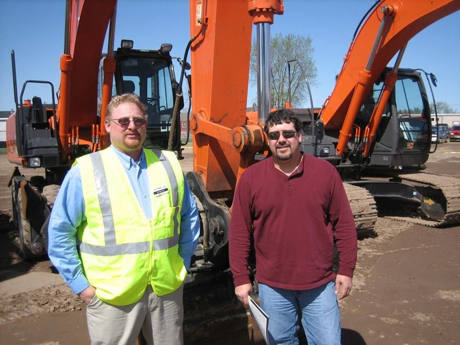 Rob Newman (L) of Nortrax shows this Hitachi Z210W to T.J. Clisch of Baraga Road Commission.